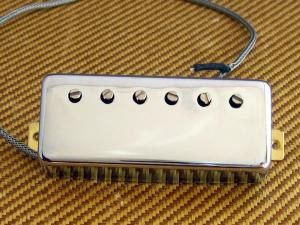 A Guitar Pickup sitting loose on a Tweed Amplifier